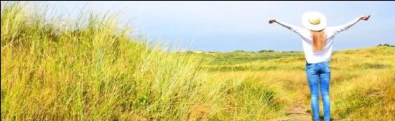 vrouw in de duinen, kijkend naar de zee