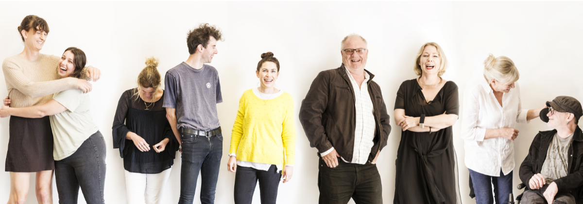 Nine people from the Be. Lab team standing in a row against a white wall smiling, hugging and laughing.