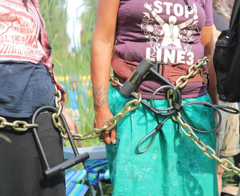 Two people head and leg cropped out, chains and bicycle u-locks around their bodies. One person's t-shirt reads Stop Line 3.