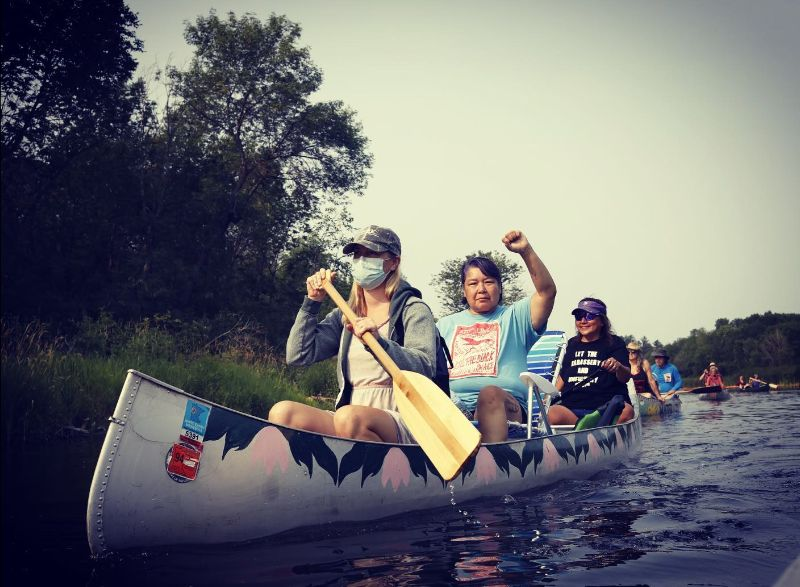 3 canoes paddling along the river. Woman in front with an oar. Behind her in the first canoe two indigenous women water protectors one with fist raised.