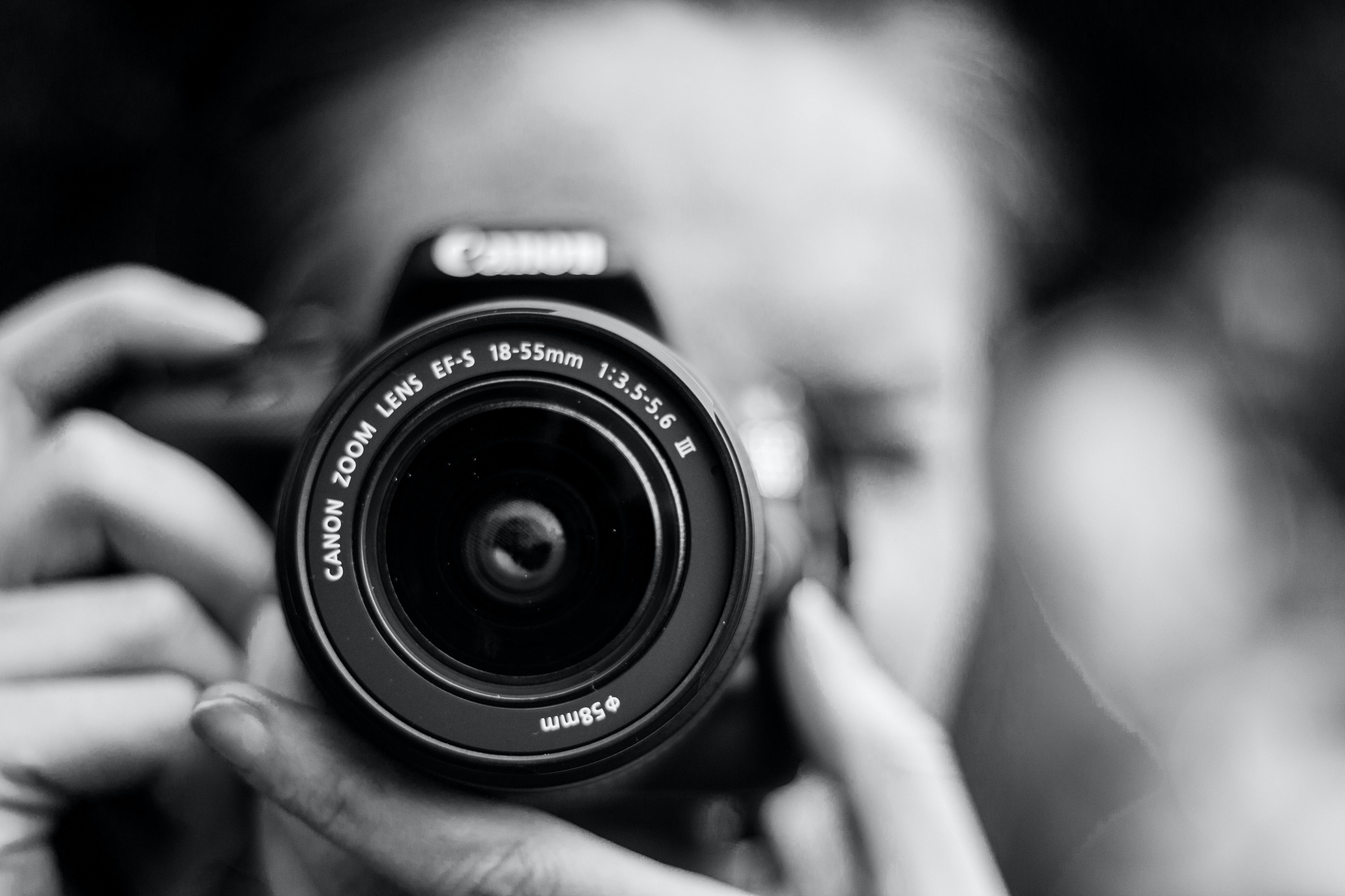 A woman holding a camera and focusing to take a shot