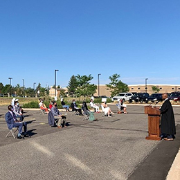 An outdoor socially distanced naturalization oath ceremony on a sunny day