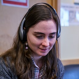 A young woman wearing earphones staring down at an unshown computer