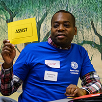 "Individual holding a sign that reads, ""ASSIST."""