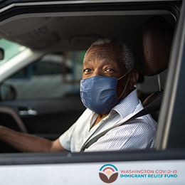 An individual wearing a nose/mouth mask in his car with the Washington COVID-19 Immigrant Relief Fund logo at the bottom on the image