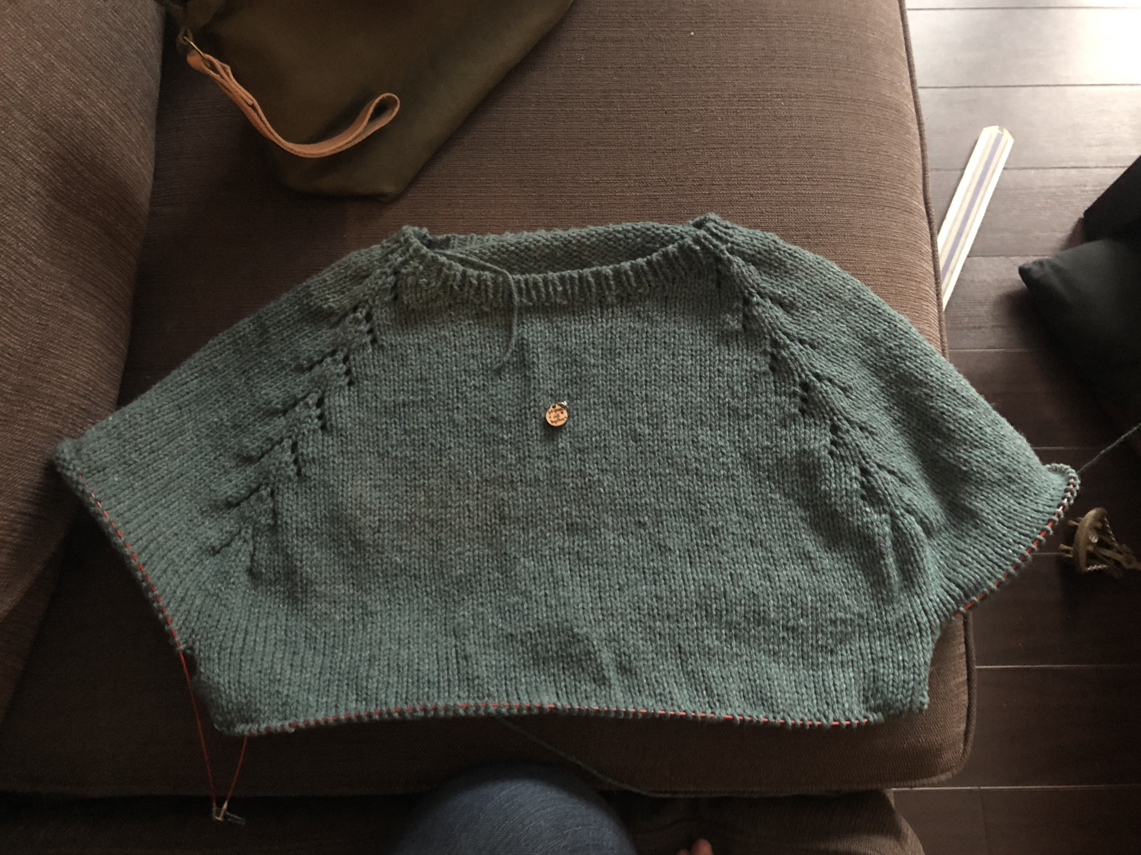 Image of a green knit sweater in progress, on a brown couch.