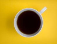 A top down view of a cup of coffee in a white mug sitting on a yellow background.