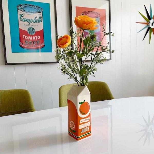 An image of orange flowers on a table in a ceramic rendering of a carton of orange juice.