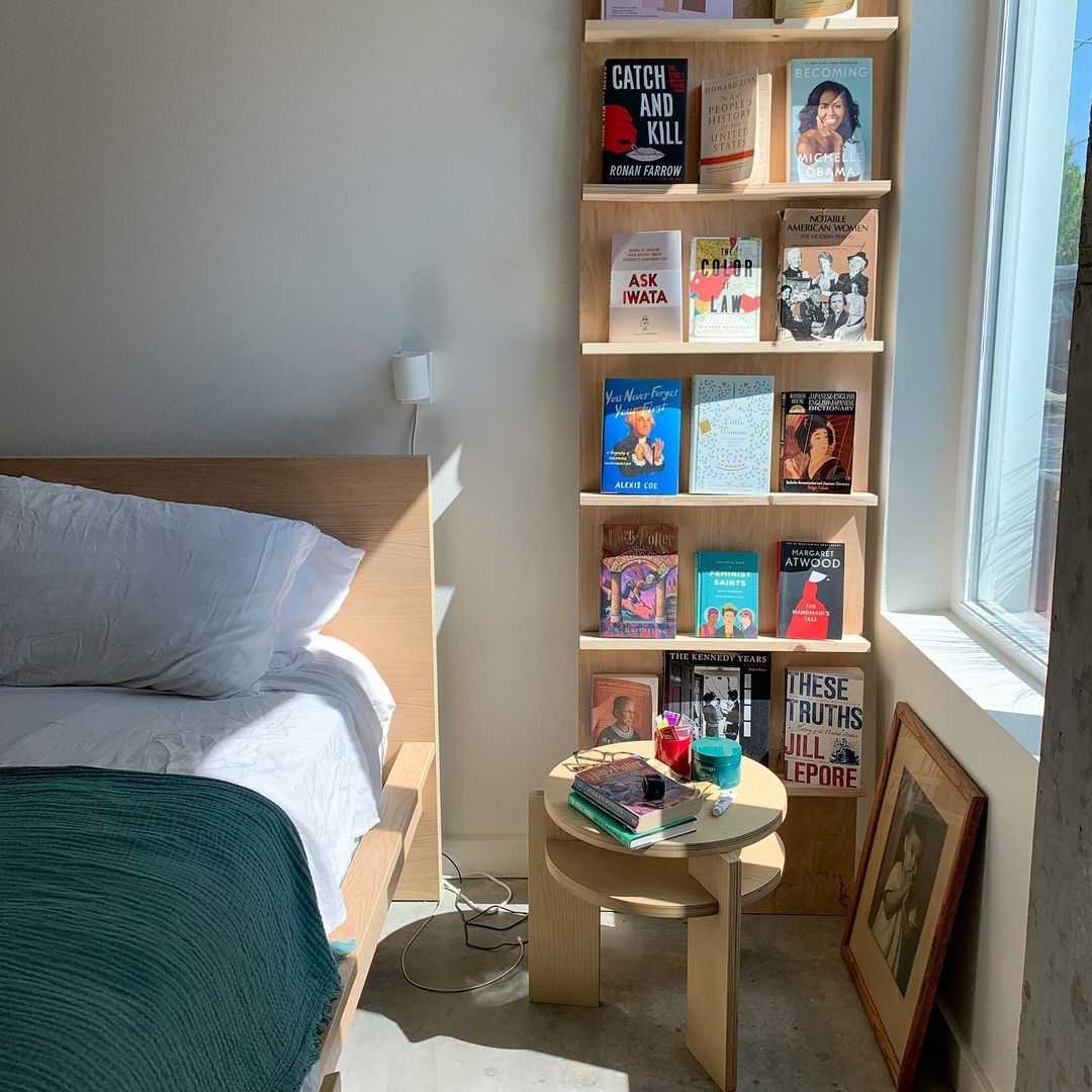 A bedroom with a bed, bookshelf, and table.