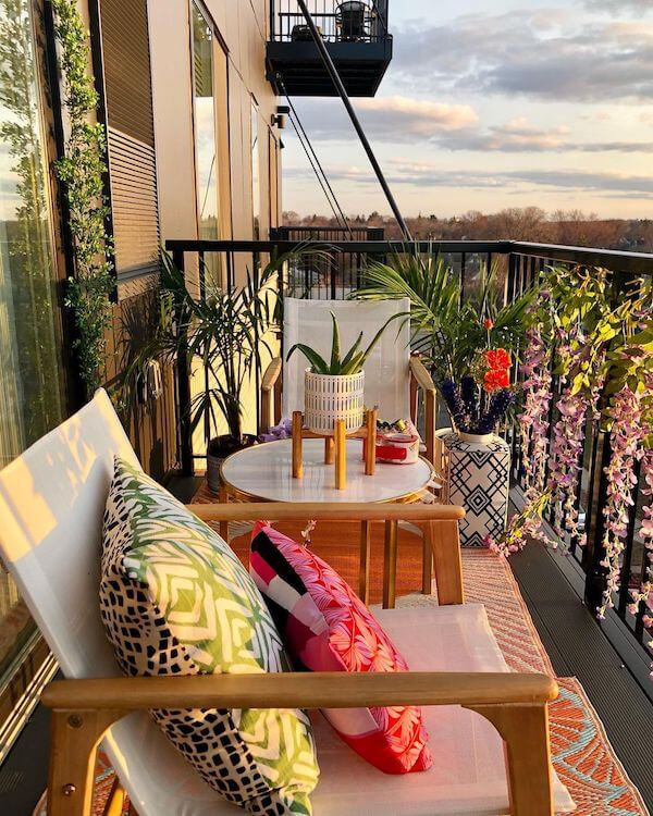 Image of Nicole Crowder's balcony setup, complete with pattered rugs, bamboo chairs, plants, florals, and bright upholstered pillows.