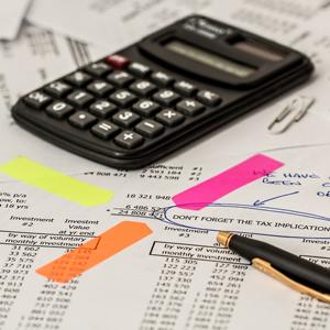 A calculator, pen and financial paperwork on a desk