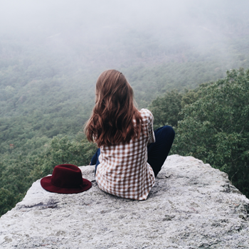 Young woman sitting on a rock gazing out over a valley
