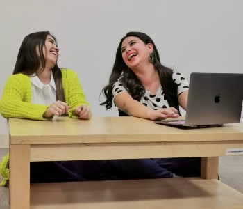 Two women at a desk with a laptop