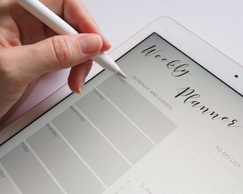 A weekly planner with a hand holding a pen