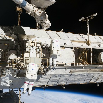 Exterior of International Space Station with two astronauts