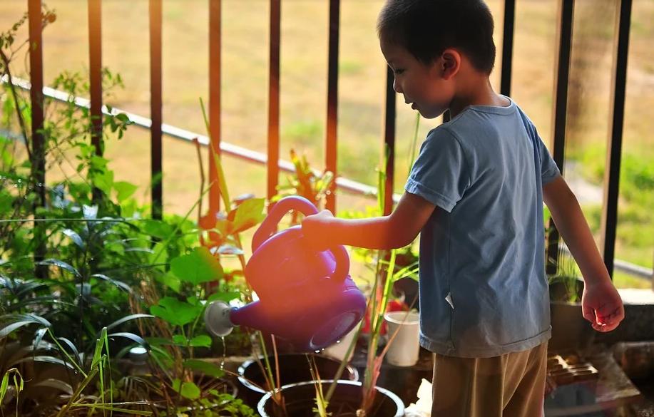 child watering garden