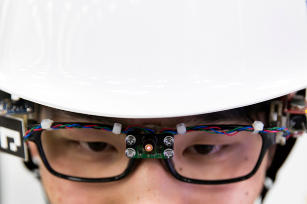 Close up of a man in a white helmet wearing glasses fitted with wires and a sensor