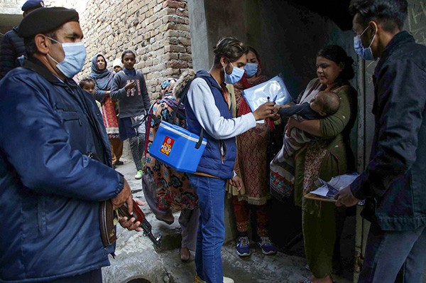 A health worker administers a polio vaccine to baby in Pakistan