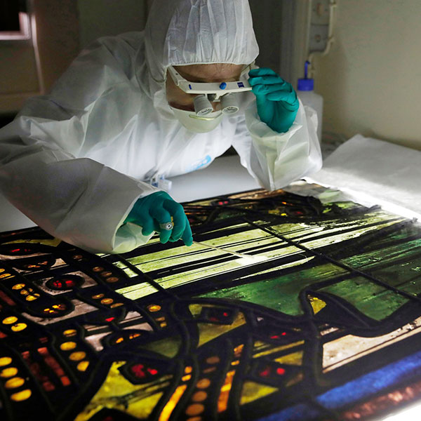 Claudine Loisel, wearing full body covering and gloves, peers closely at a back-lit stained-glass window on a table in a lab