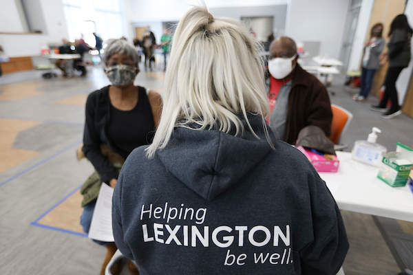 A health professional preparing to vaccinate two Lexington residents at the Senior Center.