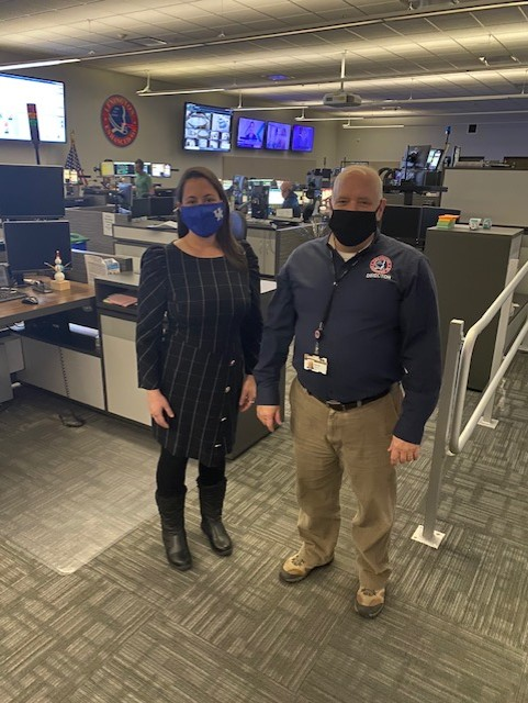Photograph of Councilmember Liz Sheehan and Director of E911 Robert Stack posing together in the 911 Dispatcher call center. Both are wearing face masks in the photo.