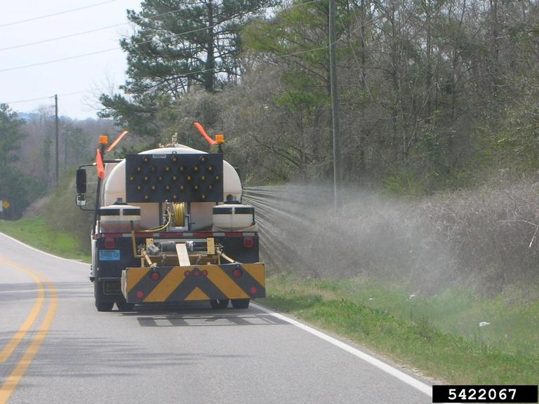 Picture of road construction truck spraying herbicide. Taken from a car driving behind the truck.