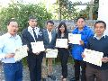 A group of people holding certificatesDescription automatically generated