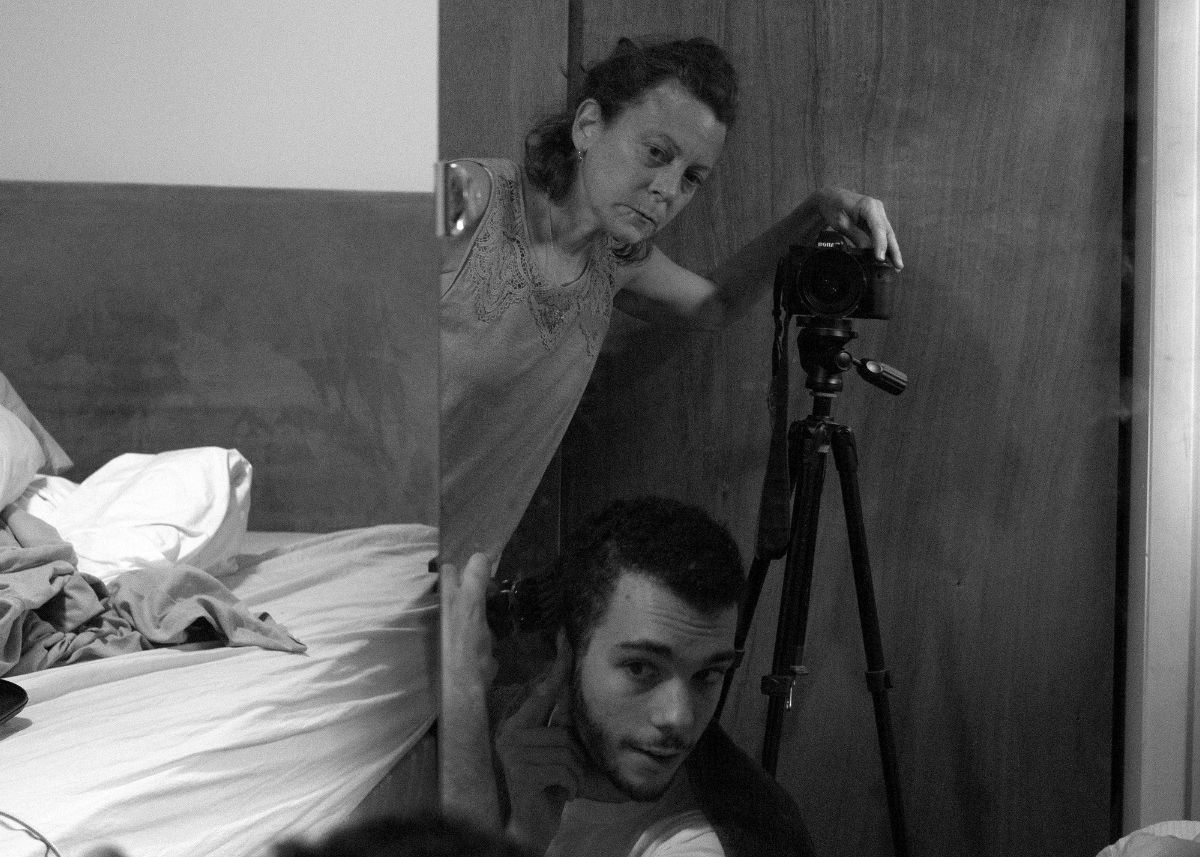 Women standing behind a camera with a man bending down, both looking in a mirror