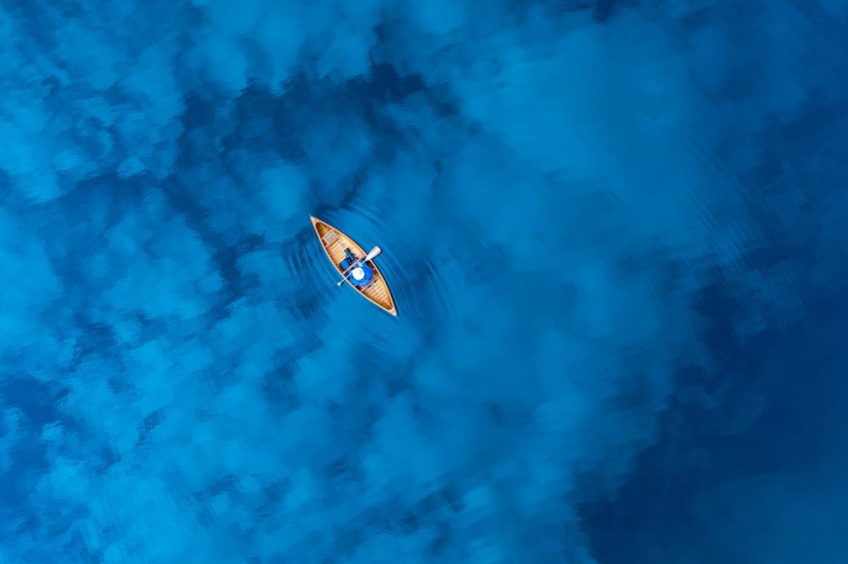 above image of a row boat in a clear blue ocean