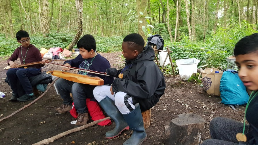 Children in the woodland playing with instruments