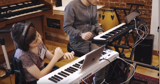 Two people playing keyboards