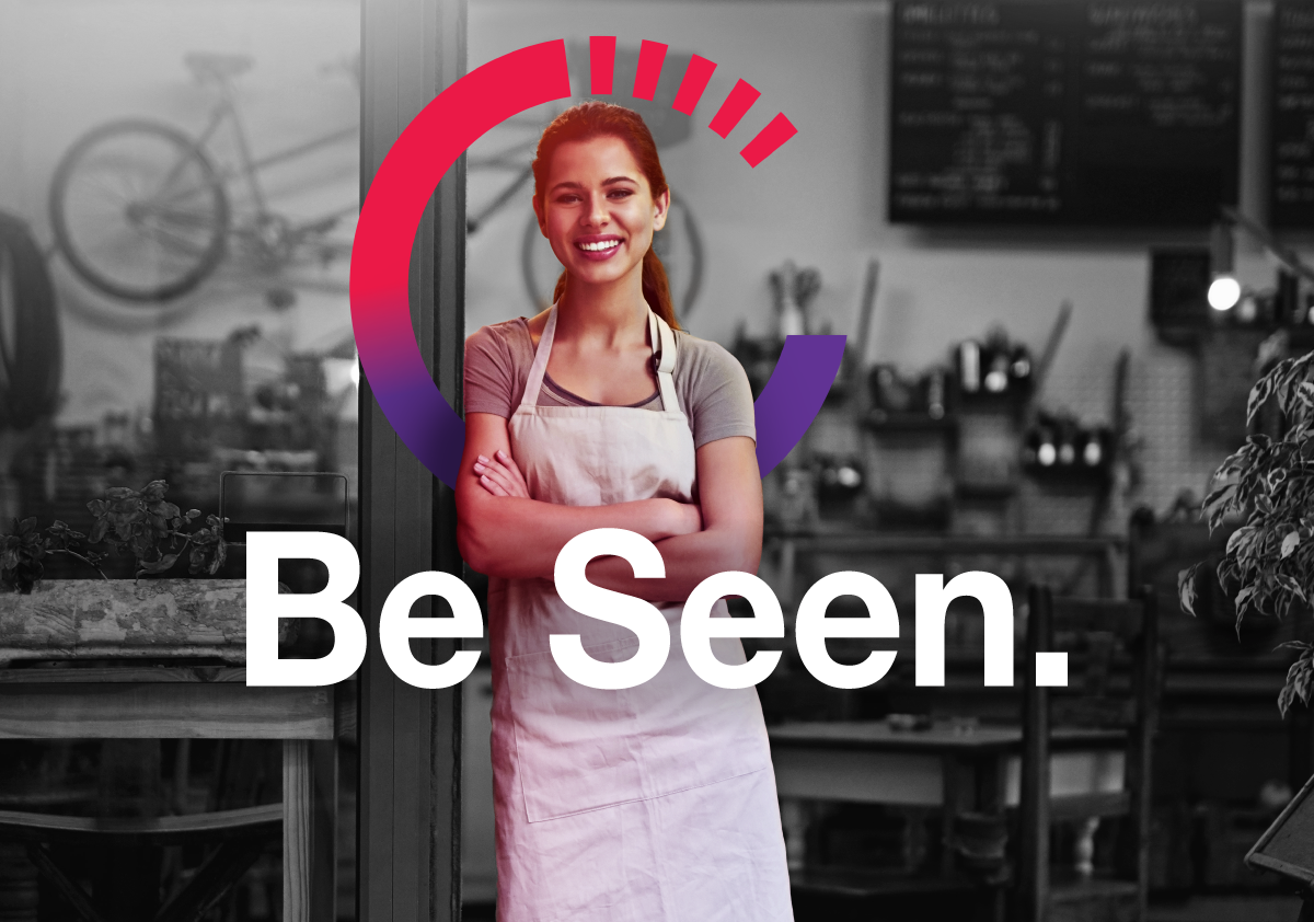 Image of smiling business women in an open cafe business shop that has the Be Seen marketing campaign text.