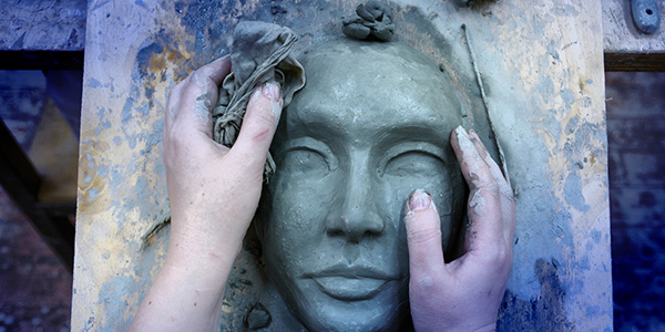 A scupltor moulds a mask from clay