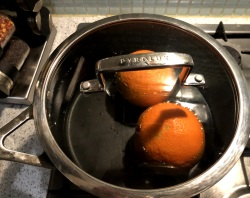 Two whole oranges in a pot of water
