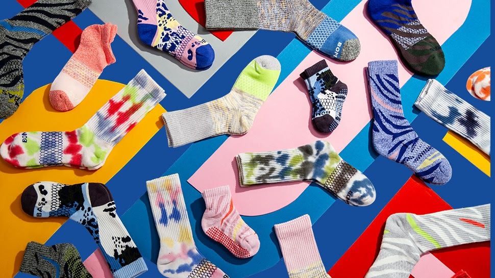 A photo of several pairs of colorful socks on top of a colorful background.