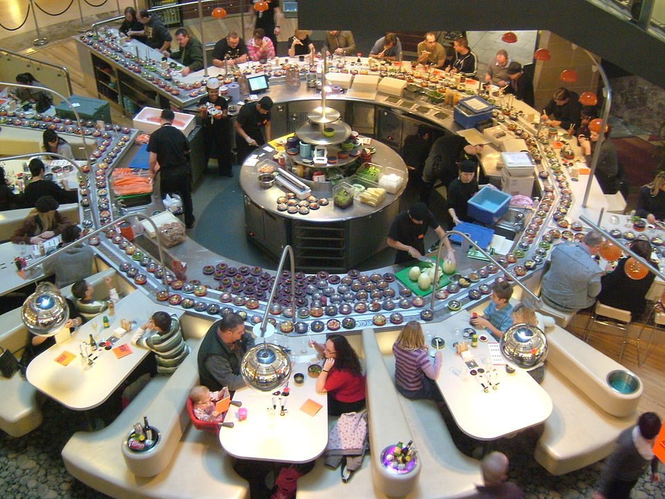 A large sushi carousel surrounded by tables