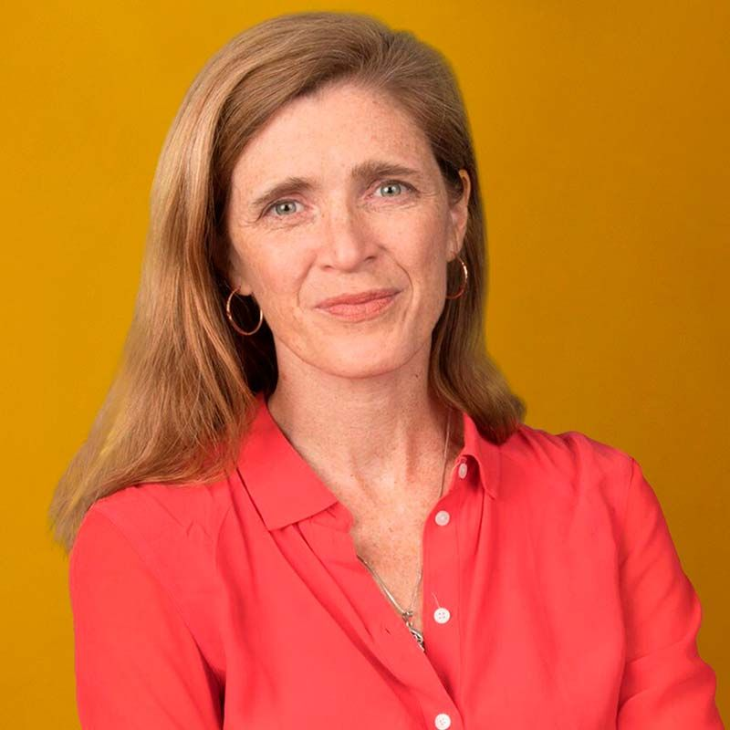 Portrait of Amb. Samantha Power wearing a red blouse against a burnt orange background.