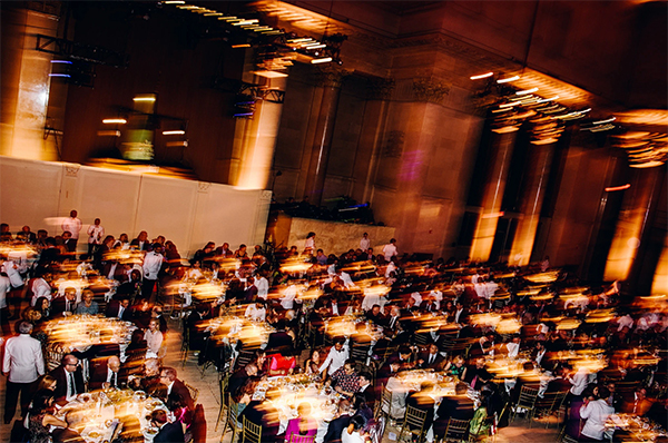 Motion shot of guests sitting at tables at a gala.