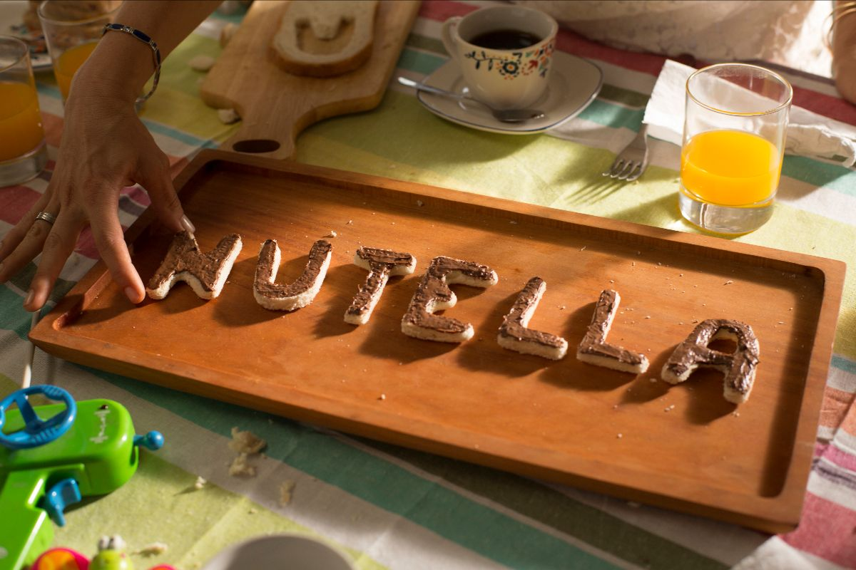 """Breakfast scene with """"Nutella"""" spelled out with pieces of bread covered in Nutella"""