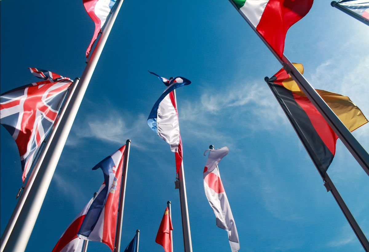 Flags from different countries against a blue sky