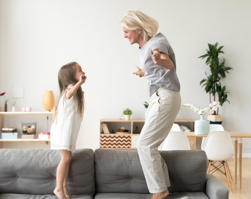 Grandma and granddaughter dancing together on the couch