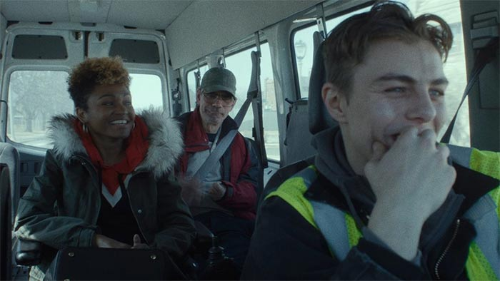 """Still from """"Give Me Liberty"""" with three smiling people inside a large white van"""