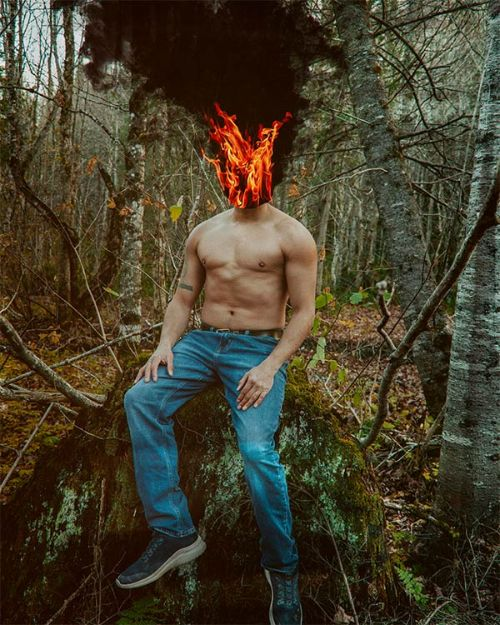 A person seated on a large tree stump, wearing a mask on fire, with a large plume of black smoke above