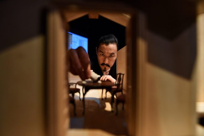 Tetsuro Shigematsu reaching into a dollhouse to place an object on a small table