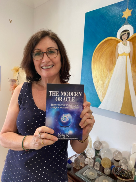 Katy K holding her brand new book - The Modern Oracle - how to tap into your unique psychic abilities