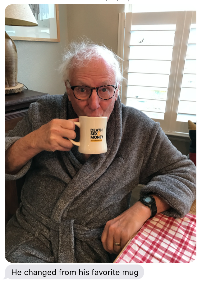 """A screen shot of a text message from Anna's mom. The screen shot includes a photo of Anna's dad, an elderly white man with messy white hair, thick-rimmed tortoiseshell glasses. He's sitting at a table covered with red and white checked cloth by a window and is wearing a gray robe, a black watch, while drinking from a beige, diner-style mug with the Death, Sex & Money logo on it in black and yellow. Part of a lamp and picture frame are in the background on the photo, and the text message below the photo reads, """"He changed from his favorite mug."""""""