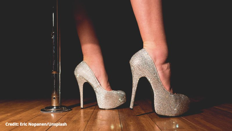 A photo of a pair of legs in silver, sparkly stilettos on a wood floor. A vertical pole is bolted to the floor behind the legs.