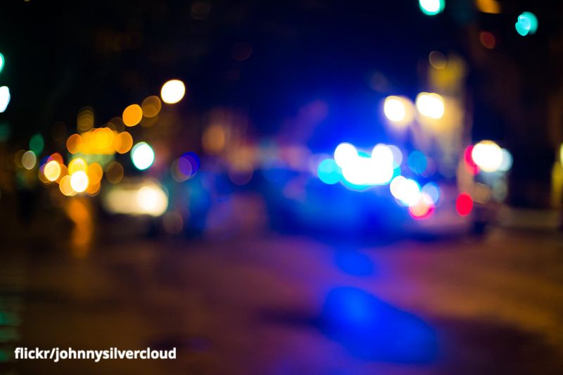 A blurred image of street lights and the lights from a police car.