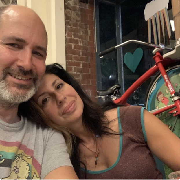 A selfie of a white couple, Brian Smith, a balding man with a salt and pepper beard and mustache. He's wearing a grey T-shirt and his wife, Jackie Cuscuna, a woman with dark brown shoulder length hair, a brown shirt with blue ribbing, and a necklace. A colorful bicycle is up against a brick wall behind them.