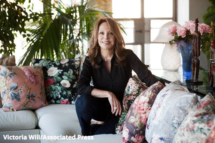 A photograph of Marlo Thomas: she is smiling at the camera and wears a black blouse and dark blue jeans. She's sitting on a beige couch surrounded by several floral pillows, and a series of plants and flowers.